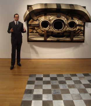 "Robert Manley, 2012 at Christie's in front of ""Untitled,"" by Lee Bontecou; ""Aluminum-Magnesium Alloy Square,"" by Carl André in foreground"